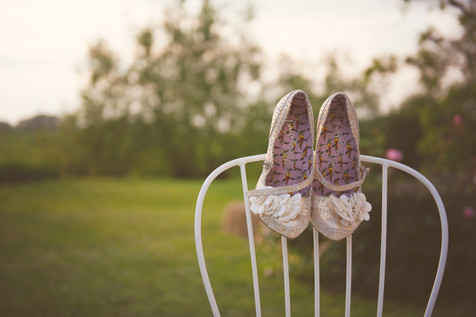 irregular choice wedding shoes hanging on the back of a white metal chair outside in the summer sunset