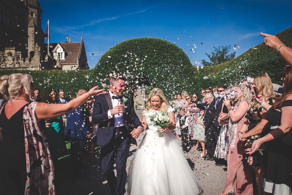 Bride and groom confetti walk in Tortworth Court grounds