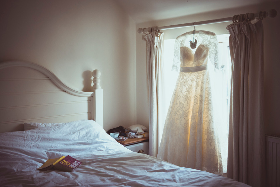 Wedding dress hanging in the window of bedroom. harry potter book on the bed