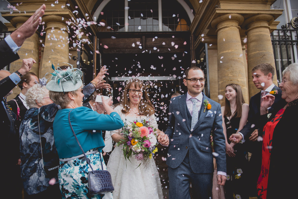 Confetti being thrown at bride and groom smiling as they exit the ceremony