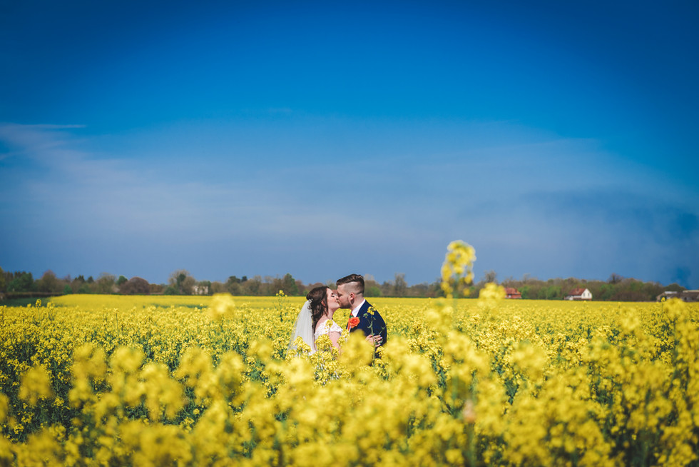 Bride and groom kissing in rape seed field on a sunny day