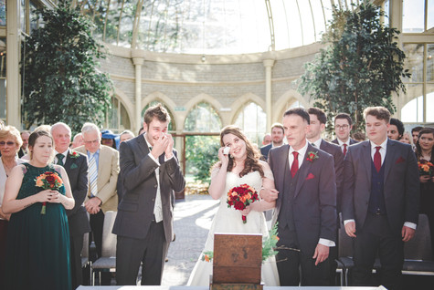 Bride and groom wiping away tears during ceremony in the orangery at tortworth court