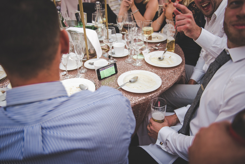 Guests watching football on phone at wedding breakfast