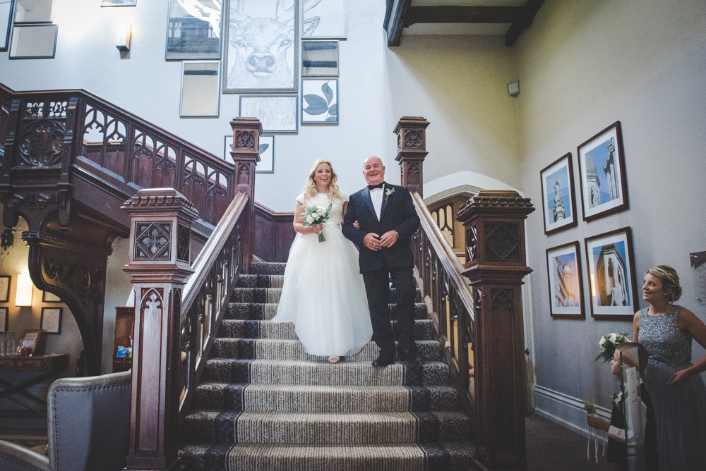 Bride and father walking down Tortworth Court staircase