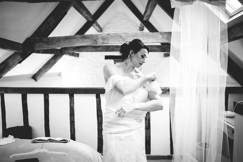Black and white photo of bride putting on her wedding dress with her veil hanging next to her from the ceiling beam. Winkworth Farm Wiltshire