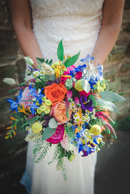 Summer bridal bouquet of flowers with pinks, oranges, yellows, blues, reds and purples