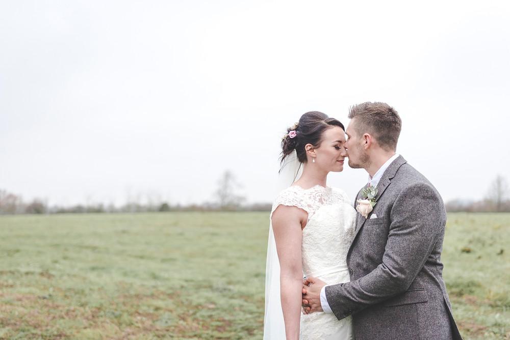 bride and groom in field gentle kiss