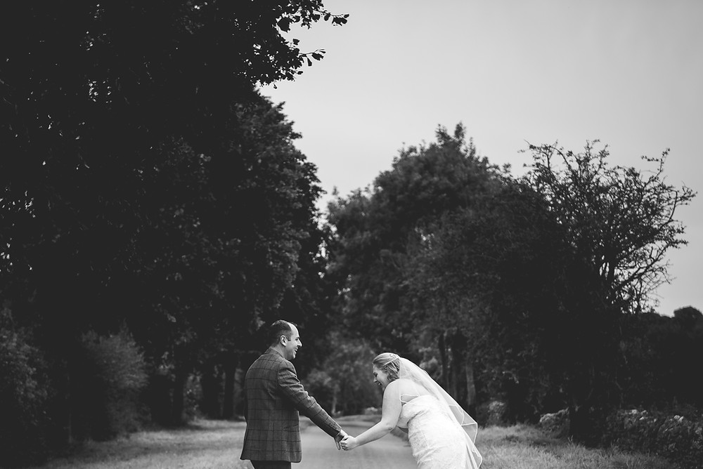 Bride and groom walking down a country lane hand in hand with bride bent over laughing