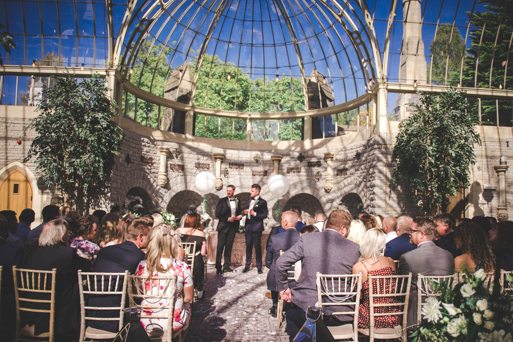 Groom and best man waiting at the alter along with seated guests in The Orangery at Tortworth Court