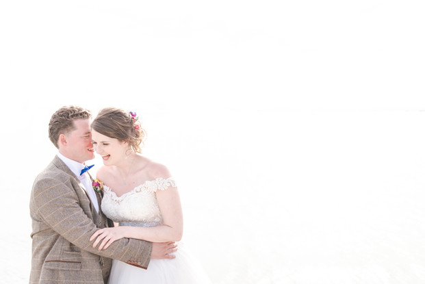 Groom whispering into laughing bride's ear on white background, Poole, UK