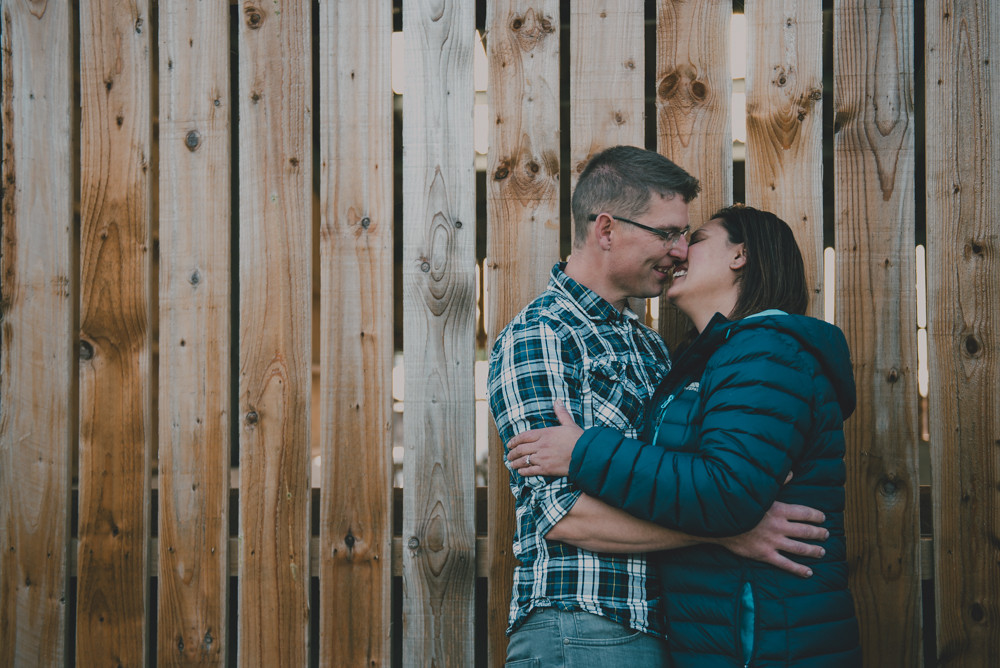 Couple kiss against barn cladding
