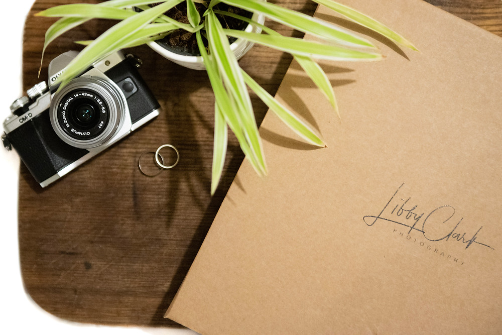 Wedding album box showing logo on wooden board with a camera, a plant and wedding rings