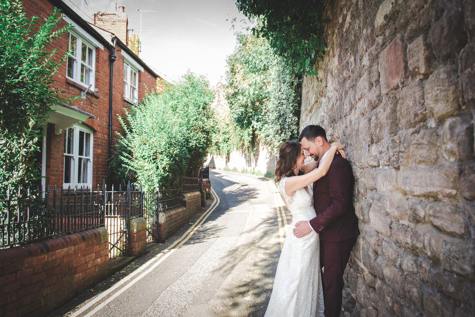 Bride and groom looking to each other in cute back street Hereford. bride her has arms wrapped loosely around grooms neck, groom has his hands on brides waist