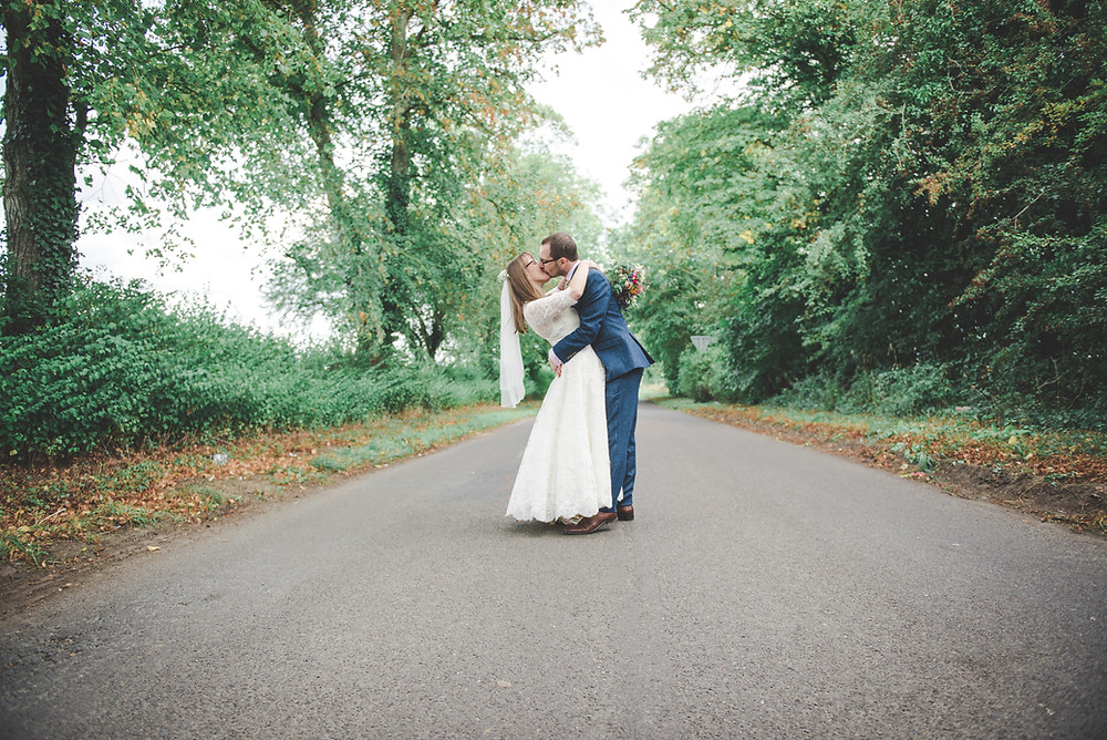 Bride and groom in english country lane