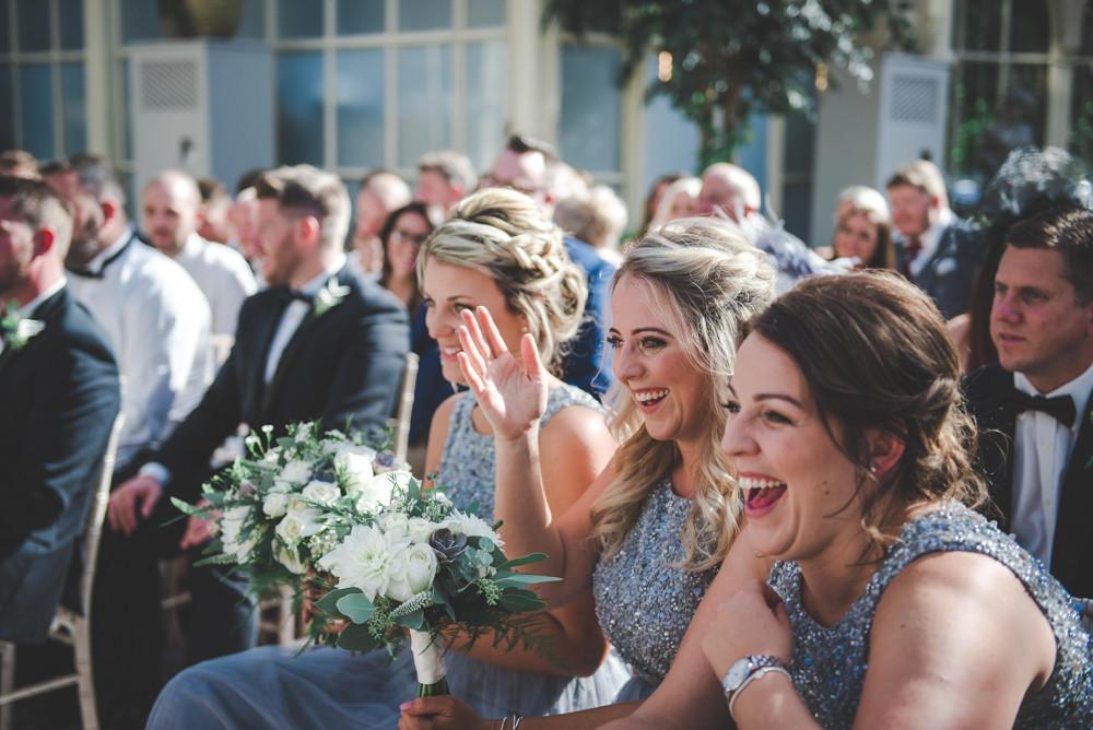 Bridesmaids laughing and waving at bride and groom