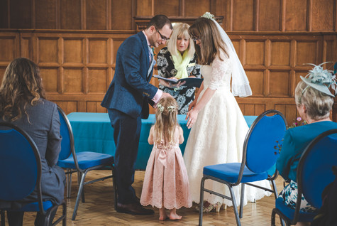bride and groom receiving their rings during ceremony. barefoot flower girl in pink dress stands between them as she passes them the rings