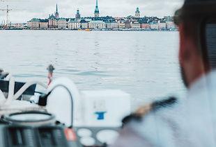 Un capitaine à bord de son bateau regardant la mer