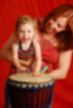 girl and woman playing djembe drum