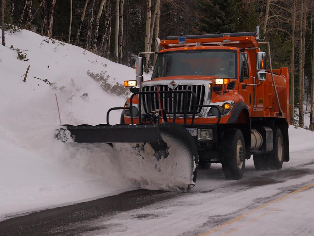 Orange snow truck, plowing road near tree bank