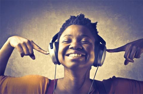 Smiling, ethnic person pointing at the headphones they are wearing