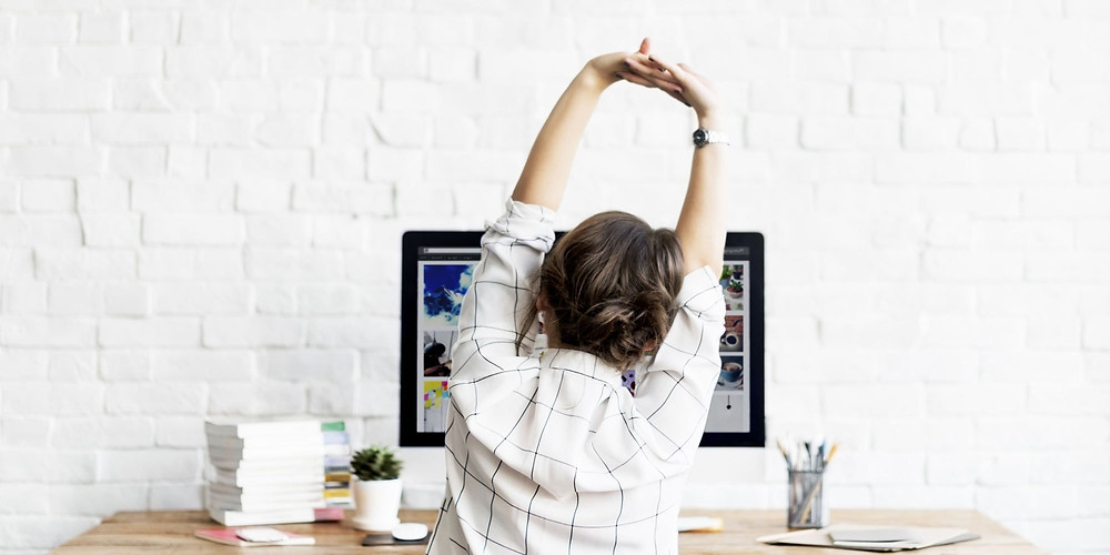 Woman at desk, stretching hands above head