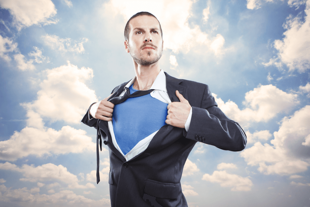 Man in business suit, holding shirt open superman style, against cloud backdrop