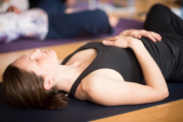 Woman lying on back on yoga mat, with hands on belly and heart