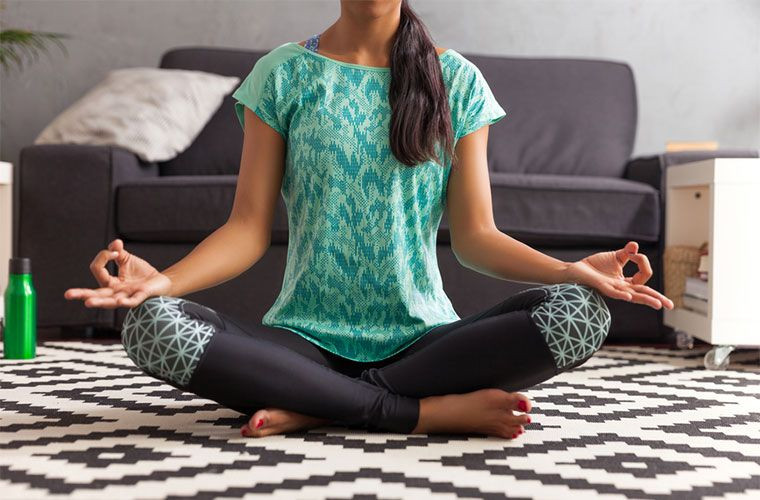 Woman in exercise clothing, seated meditating in modern living room