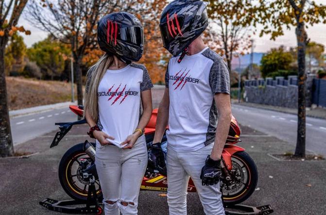 Motero y motera con camisetas moteras de garras y con pegatinas en los cascos de motos agv y pegatinas de garras, fondo de una moto deportiva suzuki.