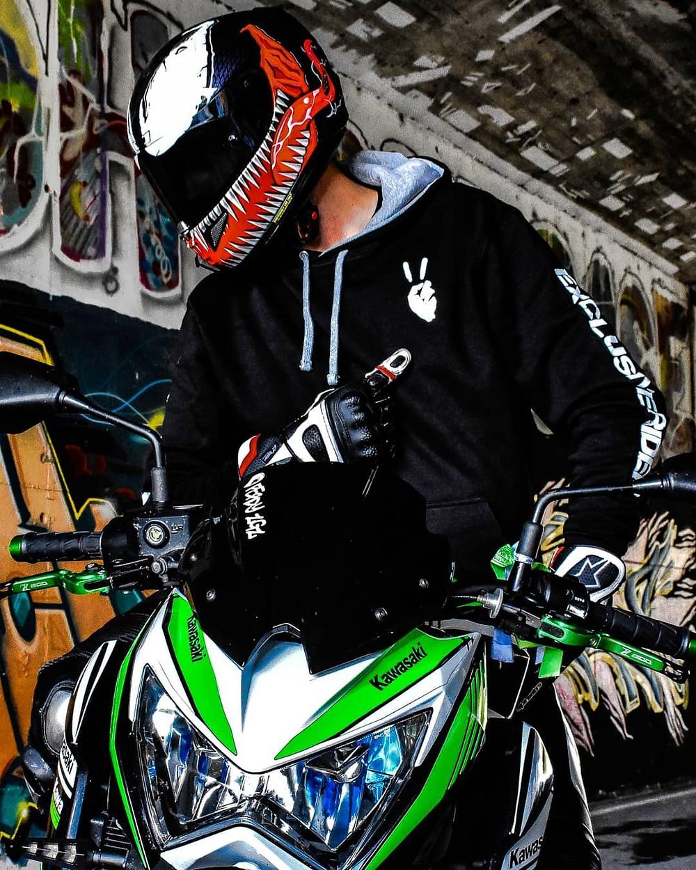 Un Motero saludando como barry sheene Tiene una moto kawasaki z800, lleva un casco hjc rpha11 y lleva una sudadera de Exclusive Rider