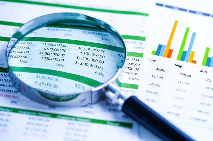 Magnifying glass placed on top of printed financial reports