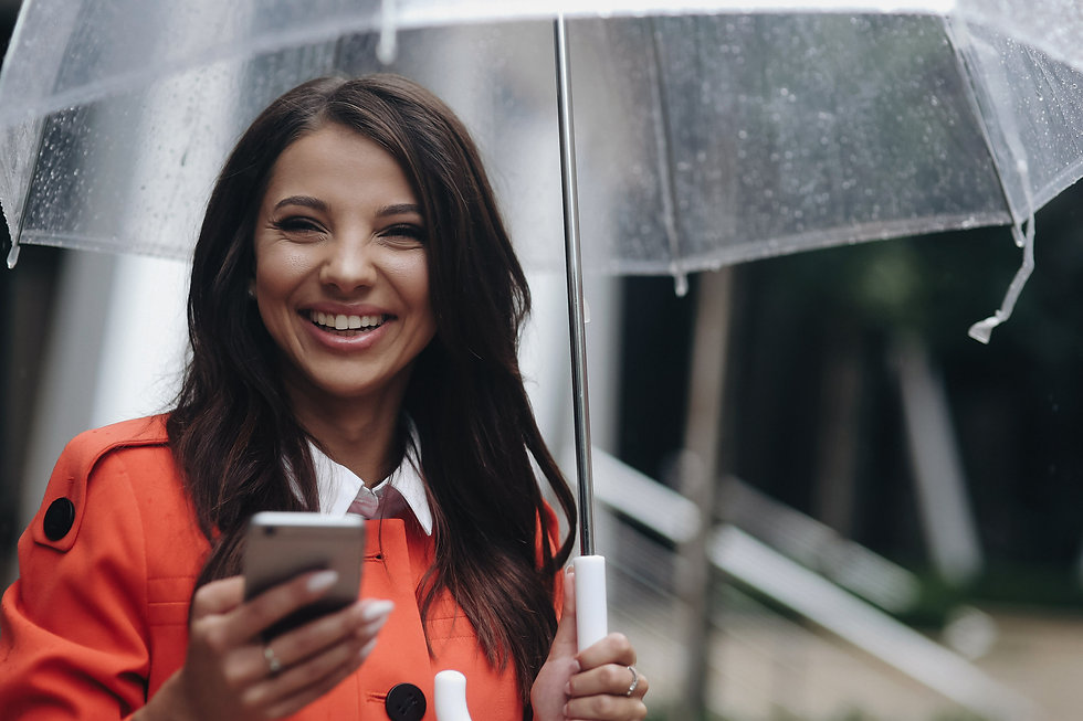 Smiling woman holding umbrella contacting Help Desk on mobile