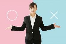 ○と×を提示する女性社員