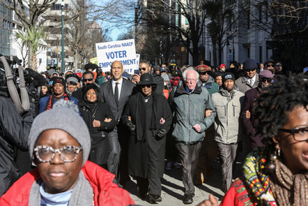 Cory Booker and Bernie Sanders march at