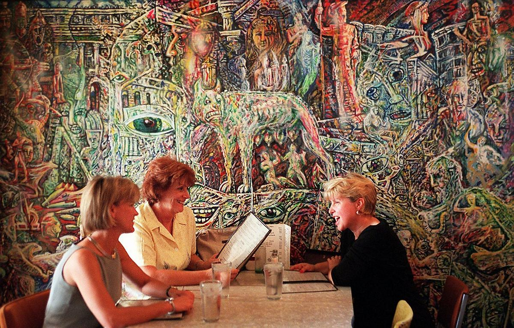 Diners at the old Mangia Italiano in front of Mangia Evolutiano - a mural by artist Wayne St. Wayne.