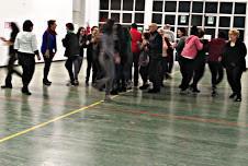 Tante persone che camminano in maniera disordinata in una stanza.