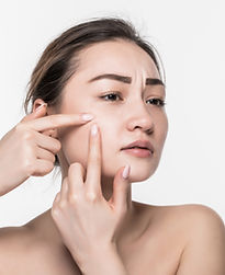 portrait-young-attractive-woman-touching-her-face-looking-acne-isolated-white-wall.jpg