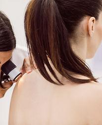 dermatologist-examining-skin-patient-with-dermatoscope.jpg
