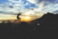 silhouette-of-man-jumping-on-rocks-at-sunset.jpg