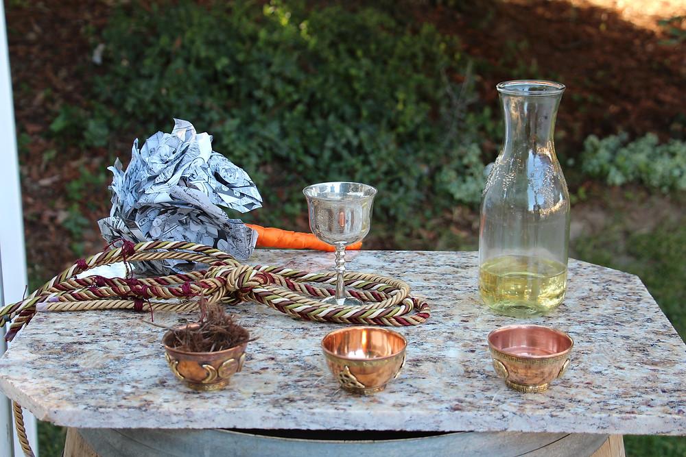 Sur une table de granite se trouve trois coupelles en cuivre. Derrière sont disposés une calice dont la base est prise dans des rubans servant à joindre les époux, à la droite de la calice se trouve une carafe de vin blanc et à gauche une sculpture de roses en papier faite à partir de pages de comics.
