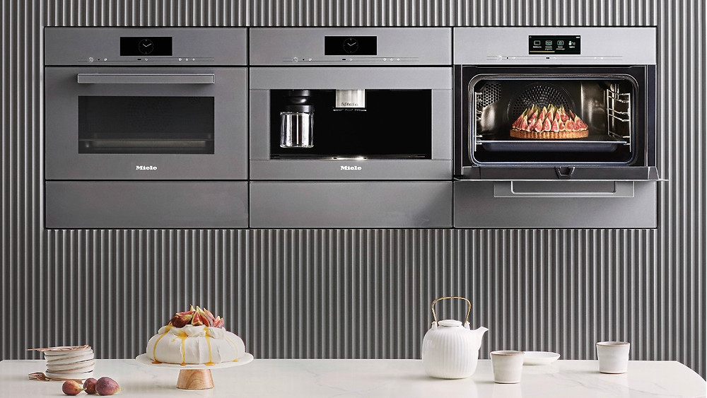 bank of stainless steel ovens and a microwave oven set into units