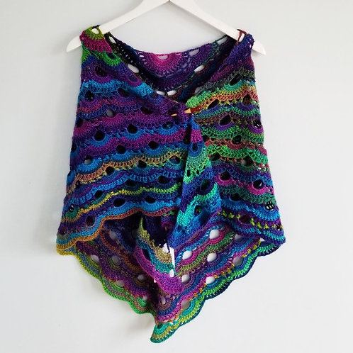 Colourful purple, magenta, blue, green shawl secured with a shawl pin