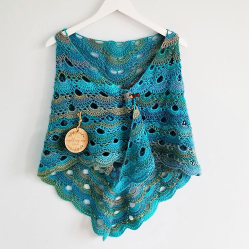 Crocheted turquoise green shawl secured with a shawl pin