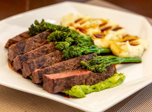 Steak and potato mash served with broccolini.