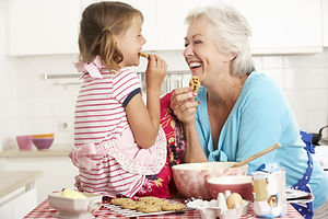 Grandmother And Granddaughter Baking In