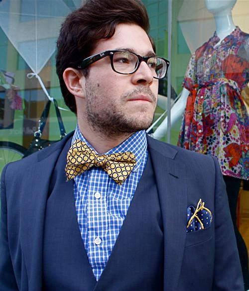 ネイビースーツと青チェックシャツとゴールドの柄蝶ネクタイ