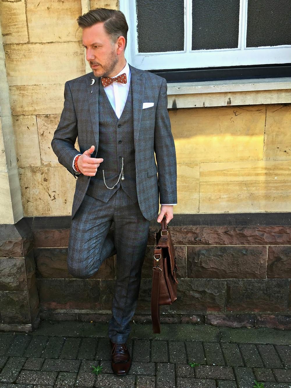 チェックのスーツと赤地ペイズリーの蝶ネクタイ