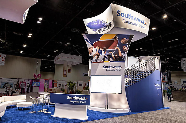 Southwest Airlines Corporate Trade Show Booth at GBTA. Two-level trade show booth with large screen monitor, white sofa seating, bar top tables, welcome desk and hanging sign.