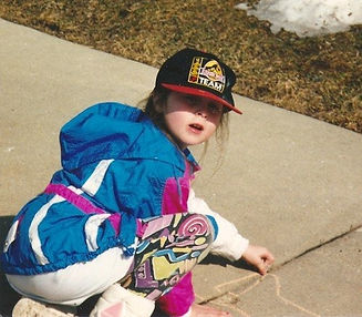 Stacy drawing with chalk as a kid in a jurassic park hat