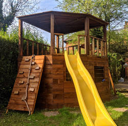 Double decker curved front playhouse, with slide, internal ladder, desk and monkey bars